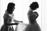 Mother helping bride put on wedding dress in black in white