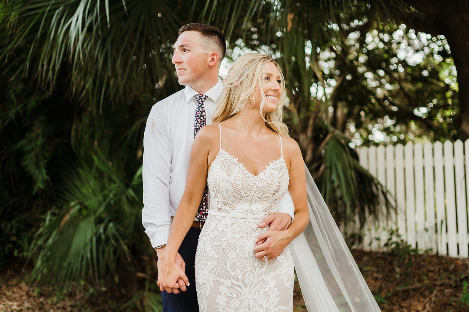 Bride & Groom holding hands looking opposite directions in lush foliage on Tybee Island Beach